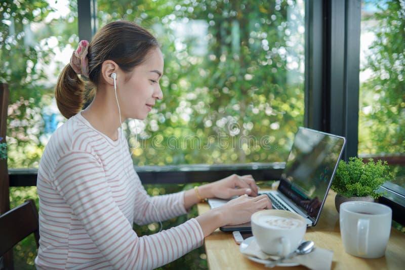 Ordenador portátil independiente del uso de la mujer joven imagenes de archivo