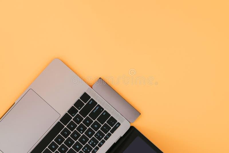 Ordenador portátil moderno con el tipo-c adaptador del USB en fondo anaranjado Concepto de la tecnología foto de archivo