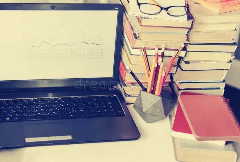 Ordenador portátil, pila de libros, cuadernos y lápices en la tabla blanca, fondo del concepto de la oficina de la educación fotos de archivo libres de regalías