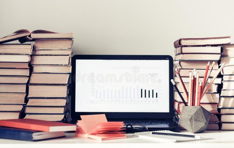 Ordenador portátil, pila de libros, cuadernos y lápices en la tabla blanca, fondo del concepto de la oficina de la educación imagen de archivo libre de regalías