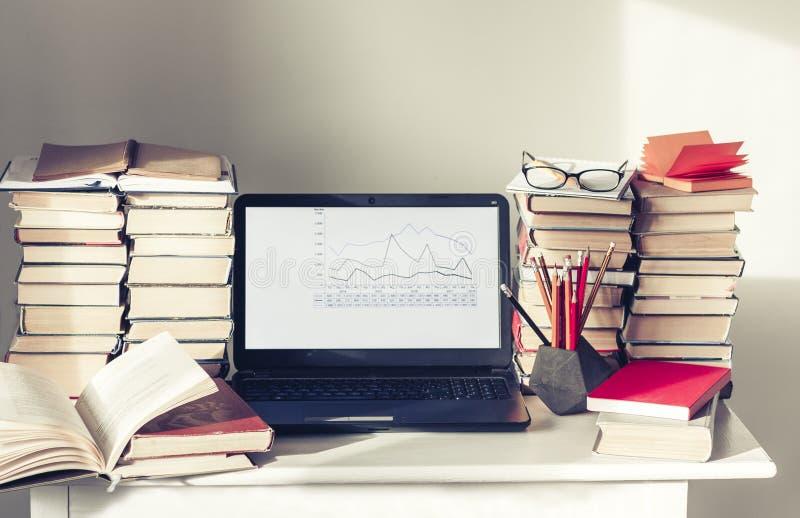 Ordenador portátil, pila de libros, cuadernos y lápices en la tabla blanca, fondo del concepto de la oficina de la educación fotografía de archivo libre de regalías