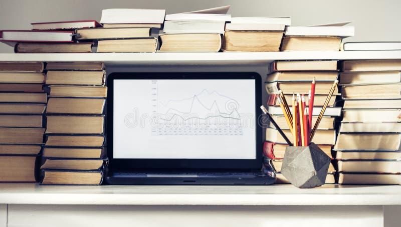 Ordenador portátil, pila de libros, cuadernos y lápices en la tabla blanca, fondo del concepto de la oficina de la educación imagenes de archivo
