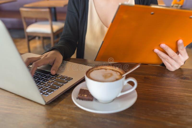 Ordenador portátil que mecanografía de la mujer joven, fichero que se sostiene y café de consumición fotos de archivo