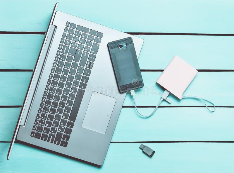 Ordenador portátil, smartphone, banco del poder, memoria USB en una tabla de madera azul Dispositivos y artilugios digitales mode fotos de archivo libres de regalías
