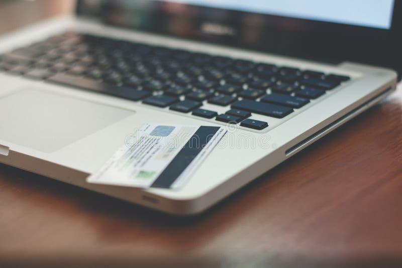 Ordenador portátil, tarjeta de banco y cuaderno foto de archivo libre de regalías
