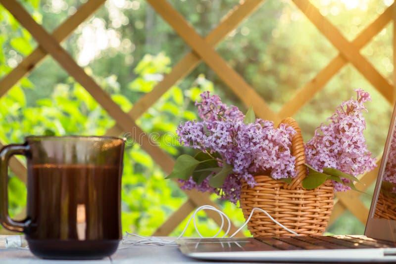 Ordenador portátil, taza de café, galletas y una cesta de flores de la lila en una tabla de madera blanca en la terraza del veran imágenes de archivo libres de regalías