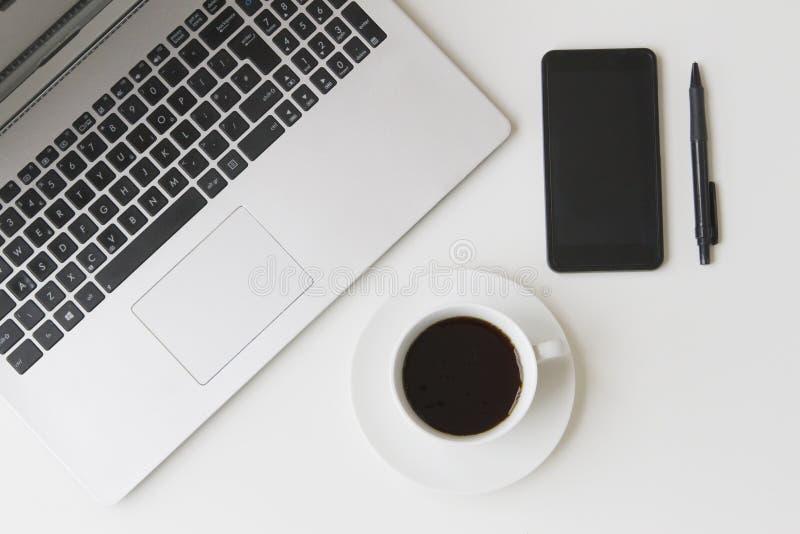 Ordenador portátil, teléfono móvil, pluma y taza de café en la tabla blanca Visión superior Endecha plana fotografía de archivo libre de regalías