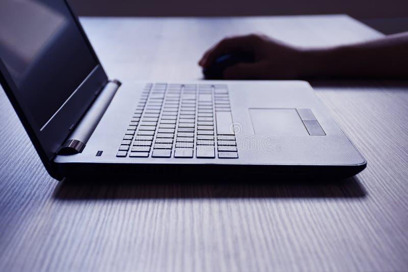 Ordenador portátil, una mano masculina usando el ordenador portátil en el escritorio imágenes de archivo libres de regalías