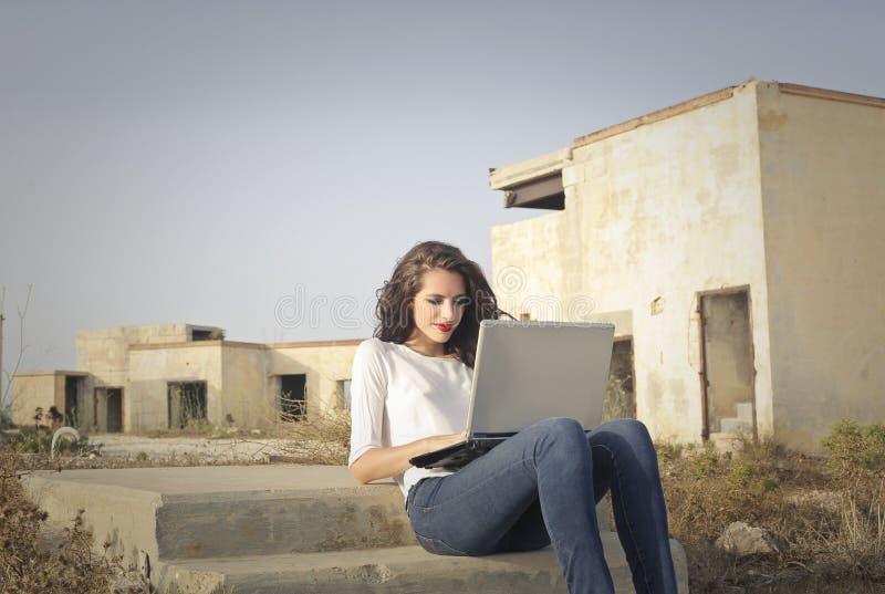 Ordenador portátil usando al lado de las ruinas foto de archivo libre de regalías