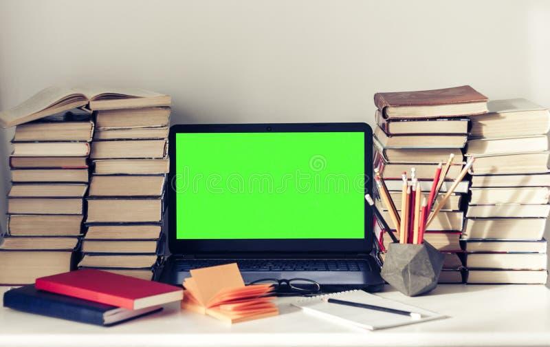 Ordenador portátil verde de la pantalla, pila de libros, cuadernos y lápices en la tabla blanca, fondo del concepto de la oficina imagen de archivo