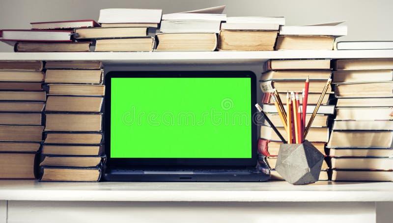 Ordenador portátil verde de la pantalla, pila de libros, cuadernos y lápices en la tabla blanca, fondo del concepto de la oficina imagen de archivo libre de regalías