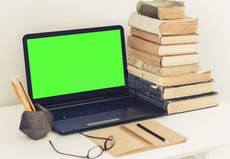 Ordenador portátil verde de la pantalla, pila de libros viejos, cuaderno y lápices en la tabla blanca, fondo del concepto de la o foto de archivo libre de regalías