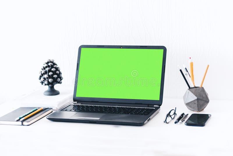 Ordenador portátil verde de la pantalla, tenedor concreto con los lápices y las plumas, cuaderno, smartphone, vidrios y pisapapel imagen de archivo