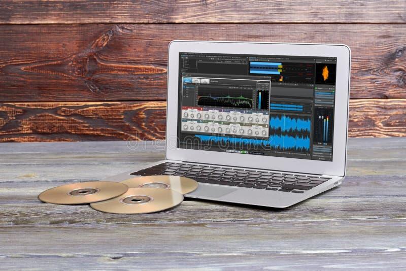 Ordenador portátil y discos en fondo de madera imagenes de archivo