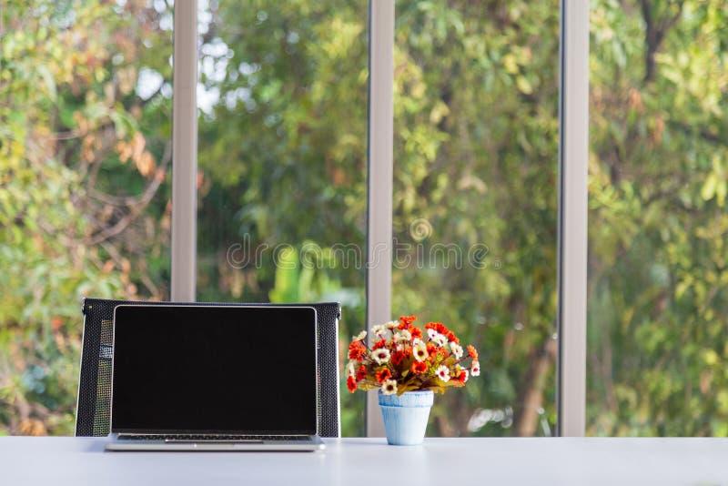 Ordenador portátil y flor artificial colorida del ramo en florero en la tabla moderna imagenes de archivo