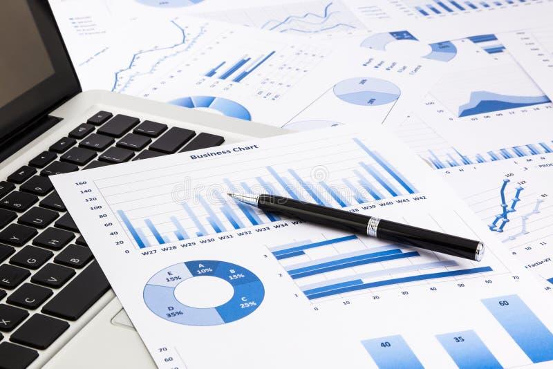 Ordenador portátil y pluma con las cartas de negocio azules, gráficos, estadística y imagenes de archivo