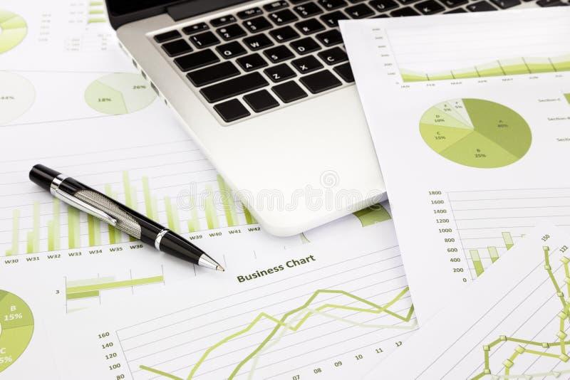 Ordenador portátil y pluma con las cartas de negocio verdes, gráficos, información a fotos de archivo