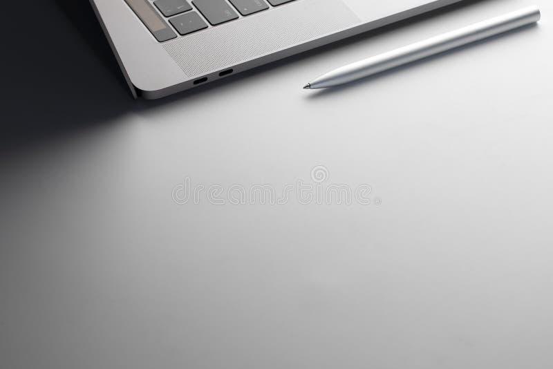 Ordenador portátil y pluma en el escritorio del negocio foto de archivo