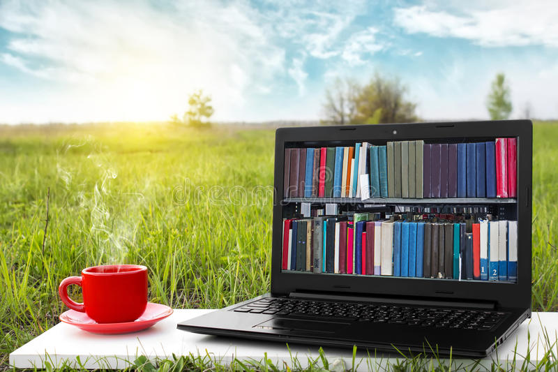 Ordenador portátil y taza de café caliente en la naturaleza pintoresca del fondo, oficina al aire libre Concepto de la biblioteca imagen de archivo