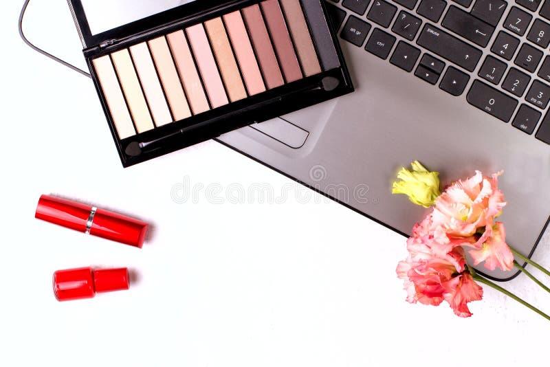Ordenador port?til con las flores y los cosm?ticos en la tabla blanca Espacio de trabajo del Freelancer imagenes de archivo
