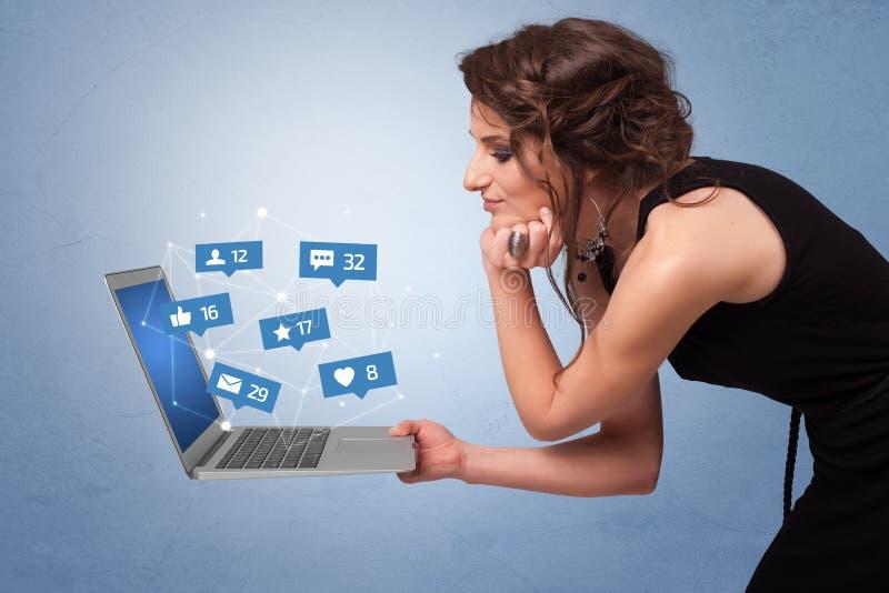 Ordenador port?til de la tenencia de Woma con notificaciones sociales de los medios foto de archivo