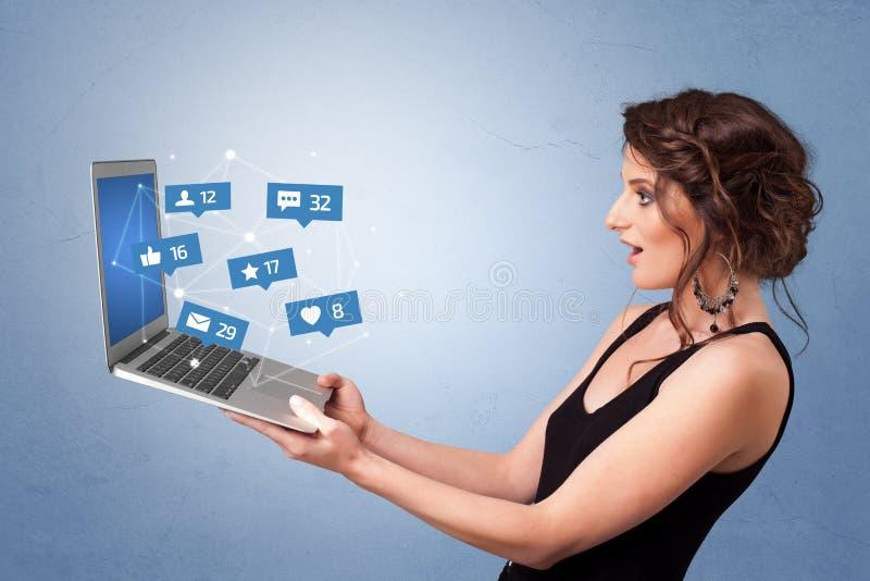 Ordenador port?til de la tenencia de Woma con notificaciones sociales de los medios fotos de archivo
