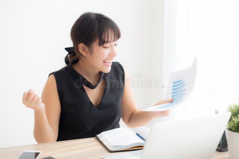 Ordenador port?til de trabajo de la mujer asi?tica joven hermosa en la oficina, empresaria que mira datos de la estad?stica del a fotos de archivo libres de regalías