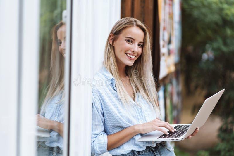 Ordenador port?til sonriente hermoso de la tenencia de la muchacha foto de archivo libre de regalías