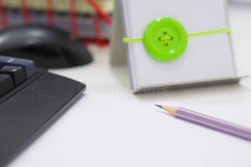 Ordenador y materiales de oficina en la tabla blanca fotos de archivo libres de regalías