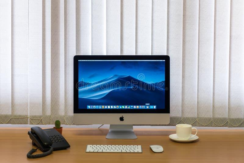 Ordenadores del monitor de IMac, teclado, ratón mágico, taza de café, teléfono, planta del cactus en la tabla de madera imagenes de archivo