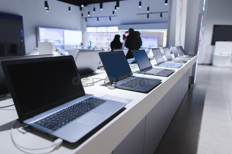 Ordenadores portátiles en una tienda moderna de la tecnología Departamento de ordenadores en la tienda de la electrónica ordenado imagen de archivo