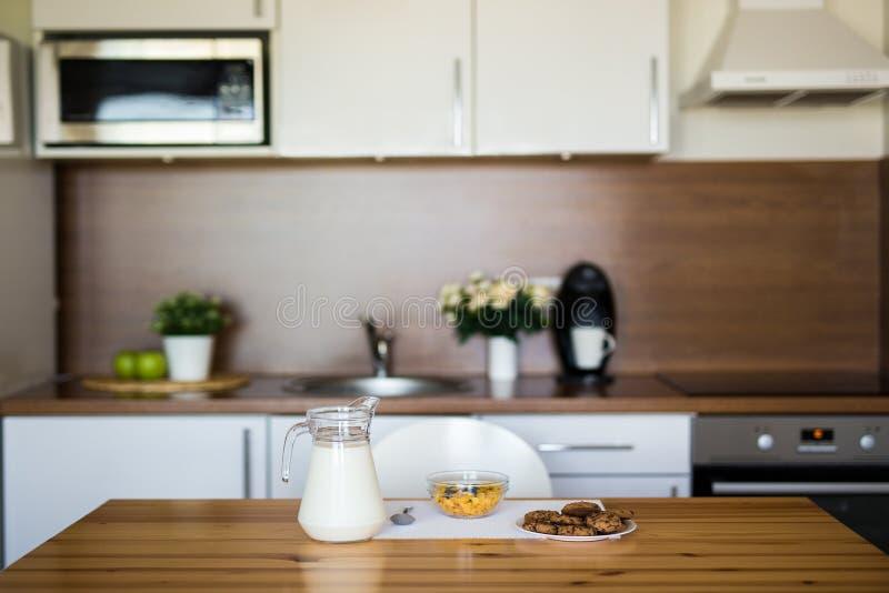 Ordenhe, flocos de milho e cookies na cozinha moderna fotografia de stock