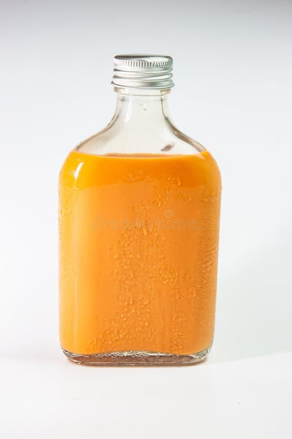 Ordenhe o chá na garrafa de vidro no fundo branco foto de stock royalty free