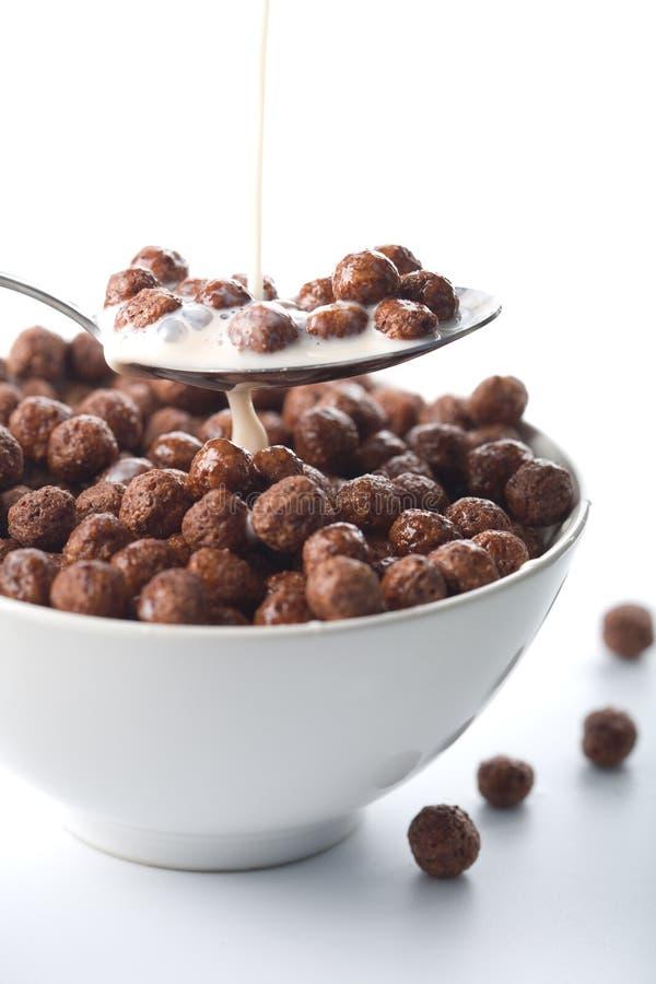 Ordenhe o derramamento na bacia com esferas do chocolate foto de stock royalty free