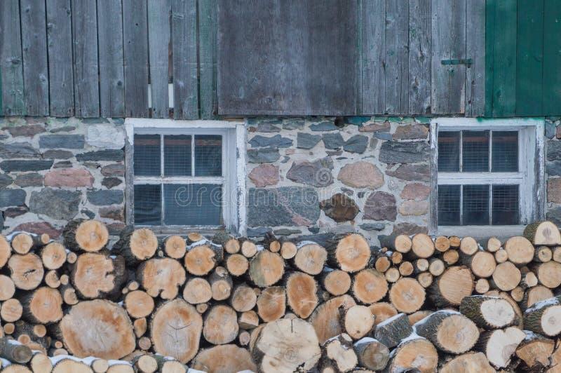 Ordentlich Staplungsbrennholz durch eine alte Ontario-Scheune im Winter lizenzfreies stockfoto