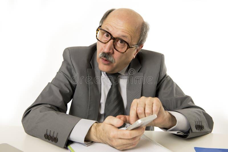 Ordentliche und saubere 60s reifen den älteren Geschäftsmann, der Handy am Schreibtischarbeiten glücklich und am Gestikulieren lu stockbild