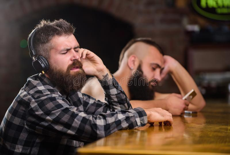 Order drinks at bar counter. Men with headphones and smartphone relaxing at bar. Avoid communication. Escape reality. Friday relaxation in bar. Hipster bearded royalty free stock photos