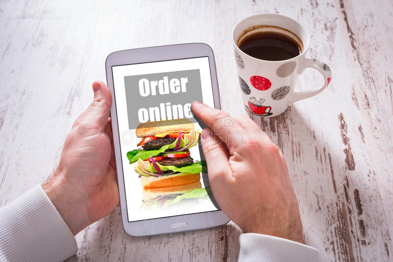 Order fast food on tablet with a cup of black coffeee. Photo on screen coming from my gallery royalty free stock photography