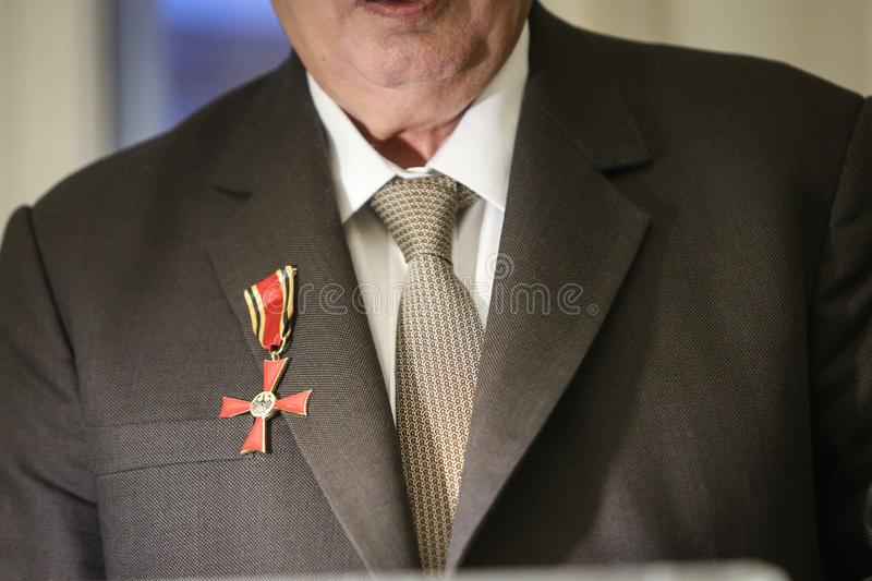 Order of Merit of the Federal Republic of Germany. Details of a man holding a cross of Order of Merit of the Federal Republic of Germany during a speech royalty free stock photo