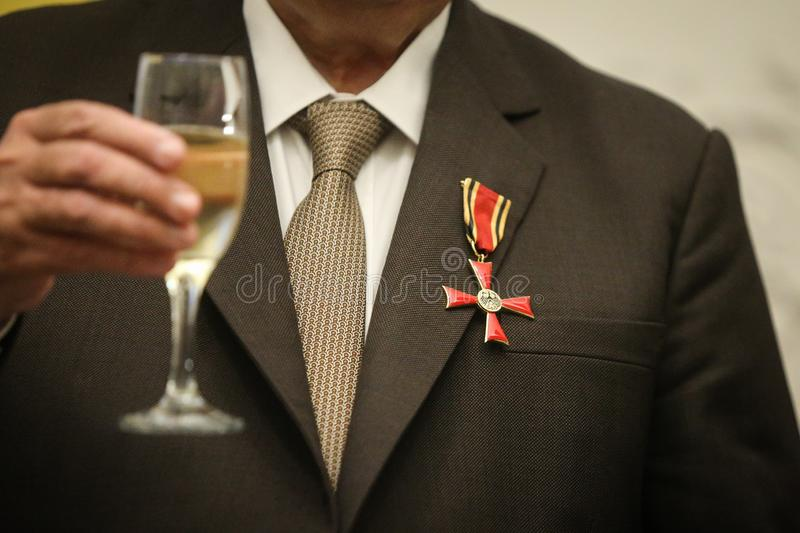 Order of Merit of the Federal Republic of Germany. Details of a man holding a cross of Order of Merit of the Federal Republic of Germany during a speech stock image