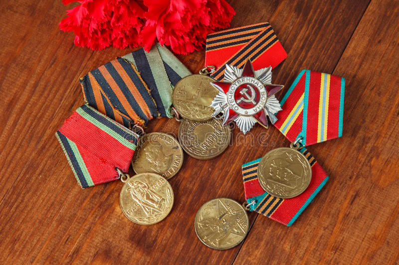 Order of the Patriotic War in St. and Medals for the victory over Germany and two red flower on a table. close up. selective focus stock image