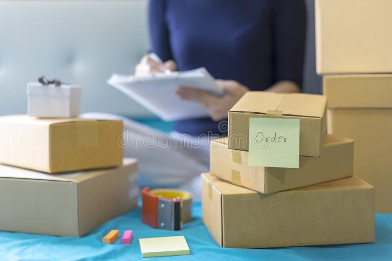 Order, Stack of packing box, Shipping parcel package and delivery shopping online. Woman writes and check packing list order.  royalty free stock photos