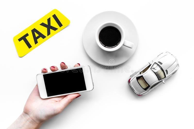 Order taxi online. Hand hold cell phone near taxi label, car toy on white background top view stock photo