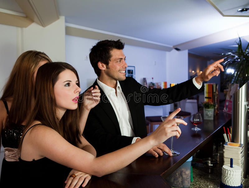 Ordering drinks at the bar. Young people ordering drinks at the bar. Focus on the girl royalty free stock image