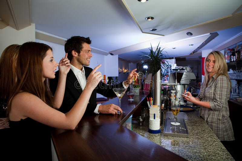 Ordering drinks at the bar. Young people ordering drinks at the bar. Focus on the men royalty free stock photos
