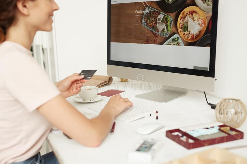 Ordering food online. Close-up of smiling woman sitting at table and using debit card while ordering food online via website royalty free stock photography