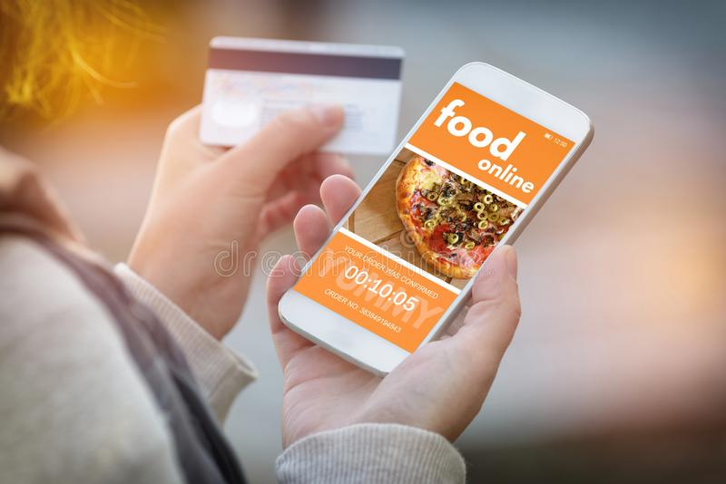 Ordering food online by smartphone. Ordering food online. Smartphone in hand and credit card in other. Concept of ordering food in office or workplace royalty free stock photography