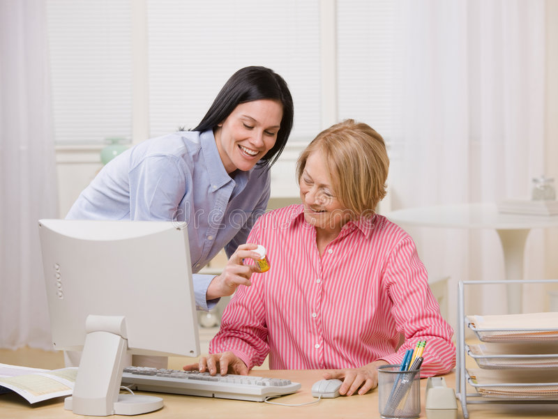 Ordering prescription medication. Adult mother and daughter ordering prescription medication online at home royalty free stock photos