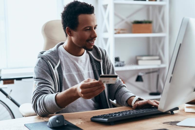Ordering something. Happy young man in casual clothing making a purchase online while spending time at home stock photos