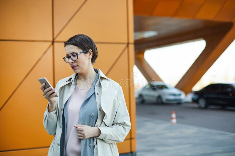 Ordering taxi online. Concentrated attractive middle-aged woman with short hair standing outdoors and using mobile app while ordering taxi online royalty free stock photo